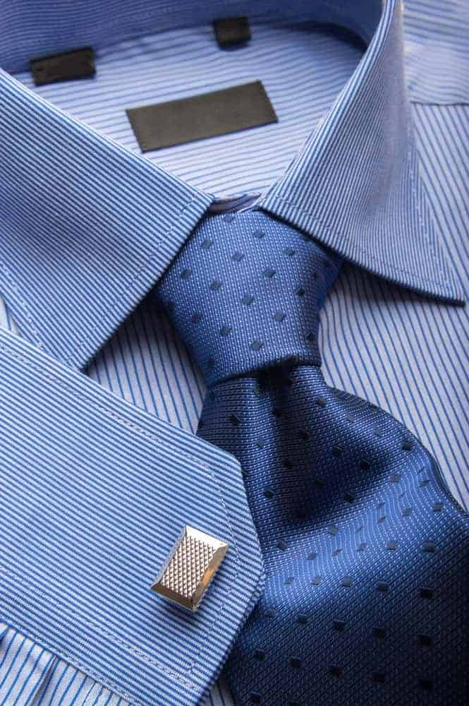 Closer look at a striped formal shirt paired with a stylish blue necktie.