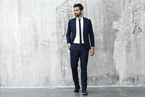 Man in suit poses against the concrete wall.
