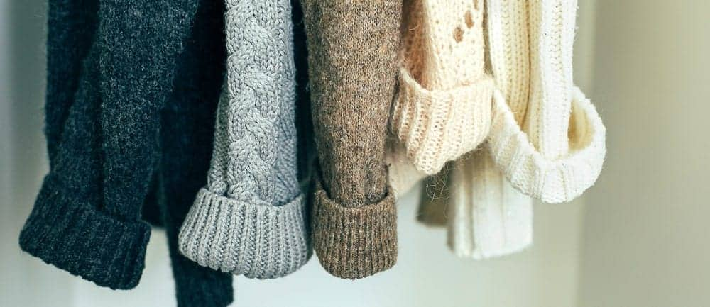 Closeup of multicolored knit sweaters.