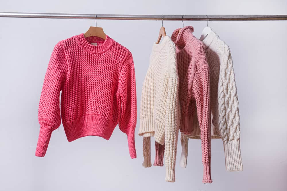 Four knitted sweaters hanging on a rod.