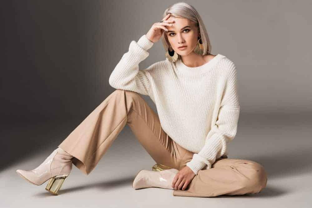 Woman posing in white trendy sweater.