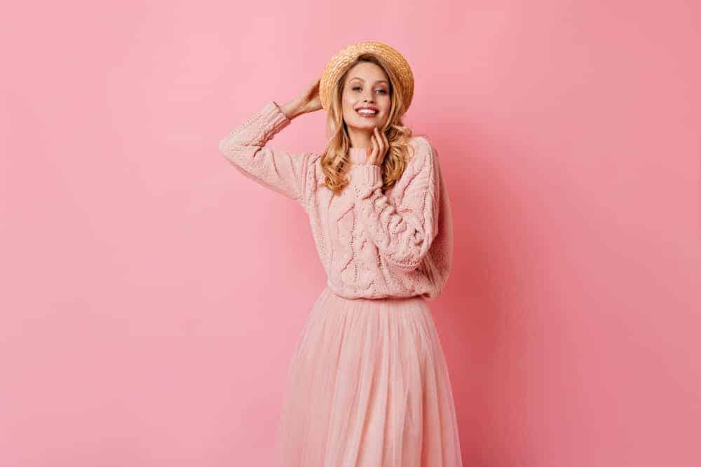 Woman in pink sweater dress blending on its background.