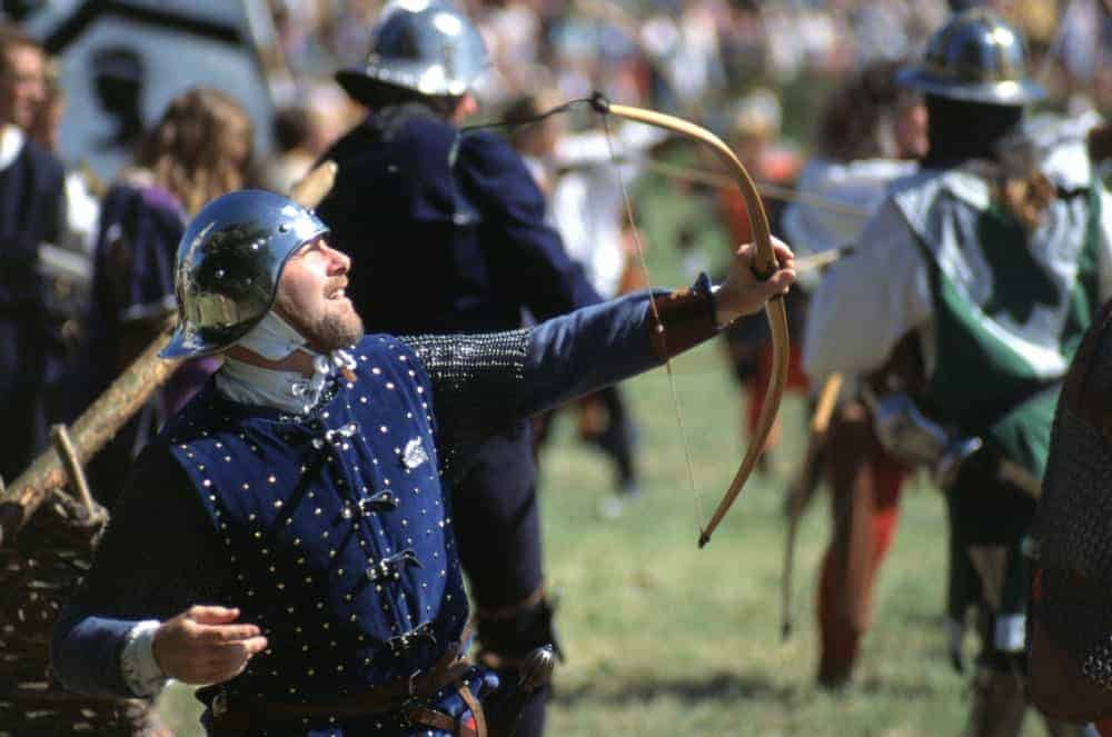 An English Archer fires an arrow from his bow wearing period Medieval helmet and tabard.