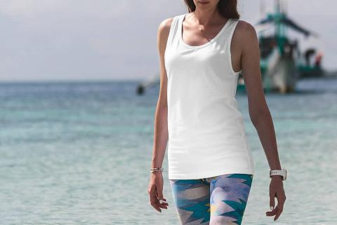 Woman in tank top and leggings standing by the beach.