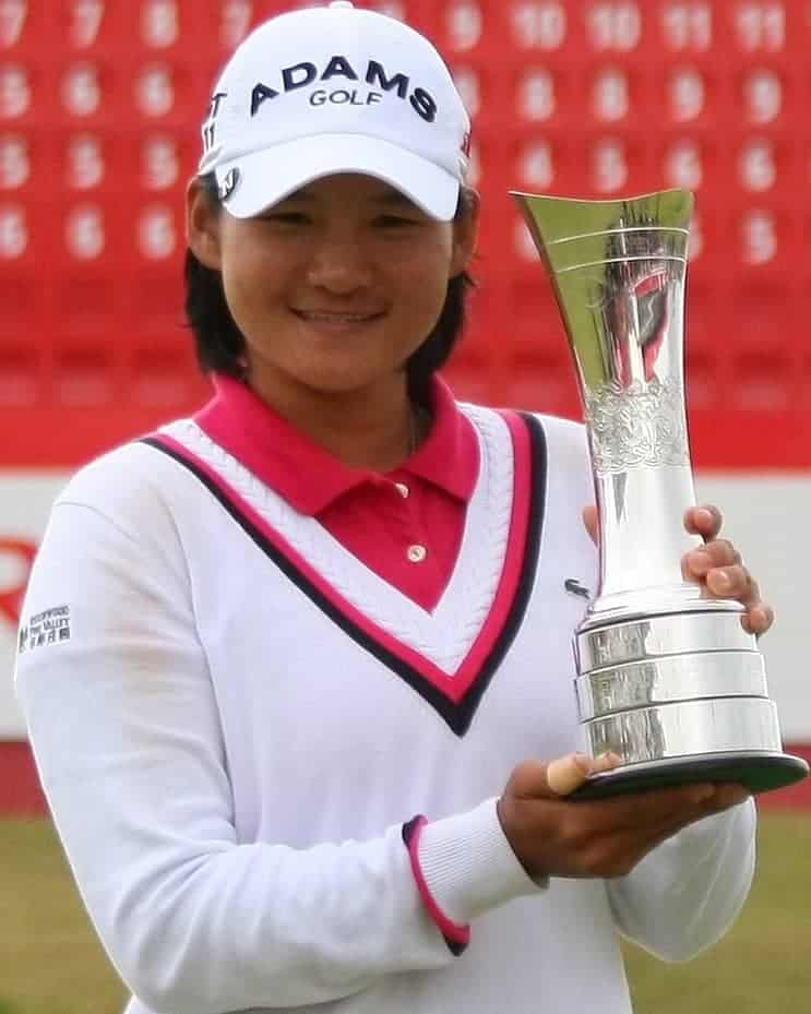 Woman in a white tennis sweater holding a gold trophy.