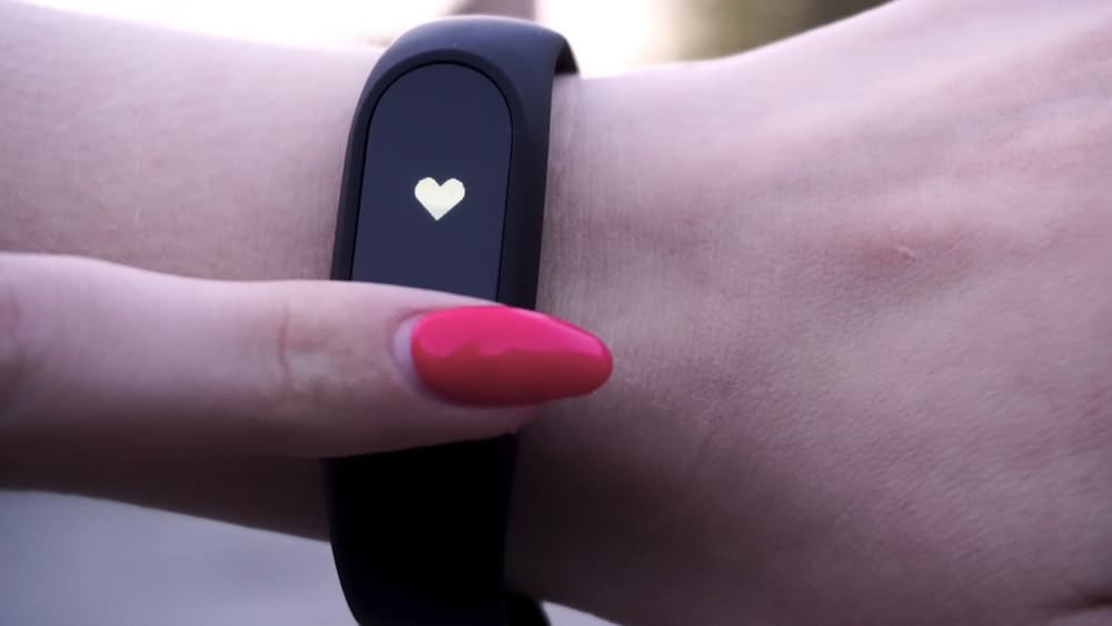 A close look at a fitbit monitoring the heart rate of the wearer.