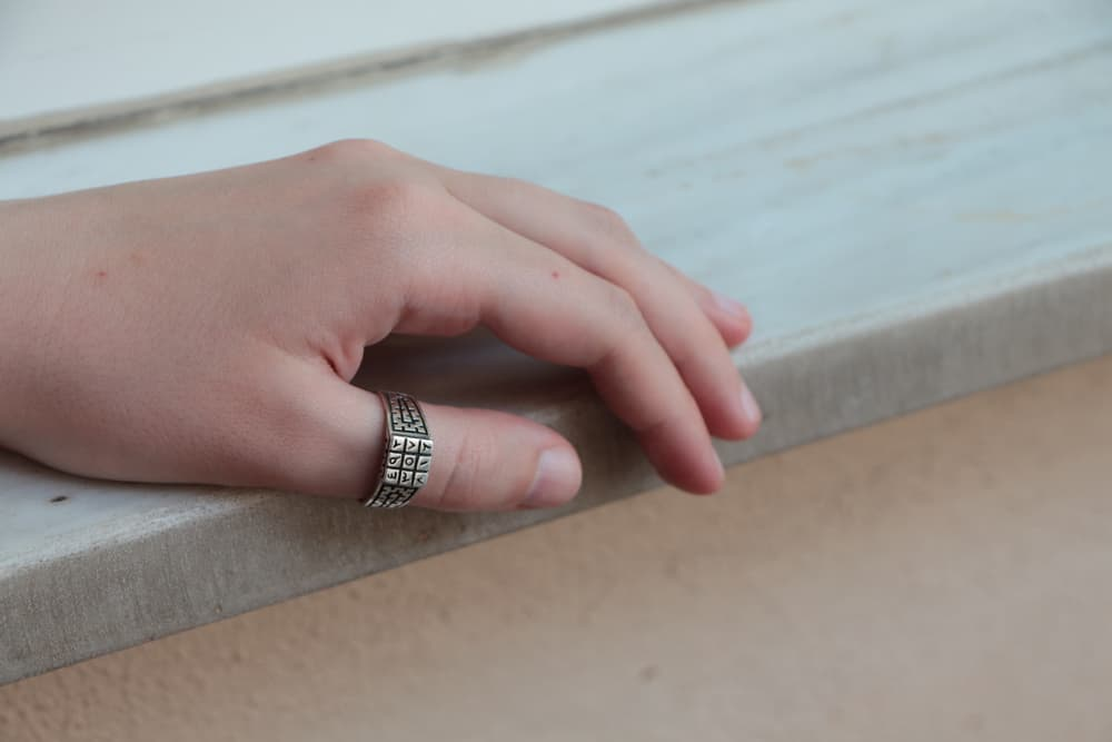 Hand with silver thumb ring.