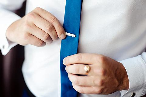Close-up of a man fastening a tie clip.