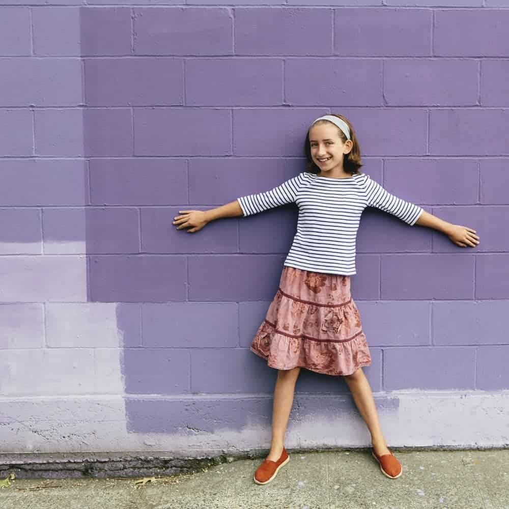 Girl in a tiered skirt stretching her arms against the purple brick wall.