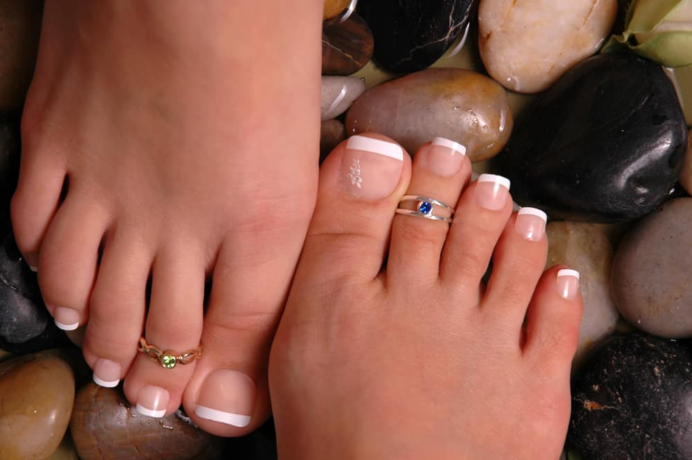 Feet with toe rings on healing pebbles.