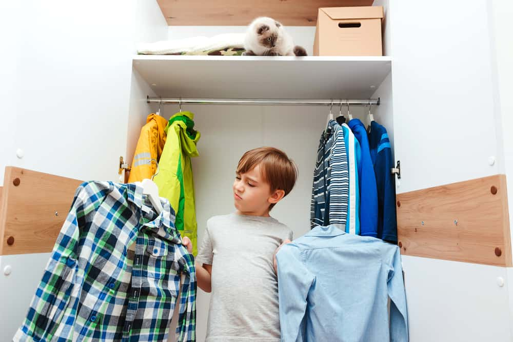 Young boy chooses clothes in the wardrobe closet.