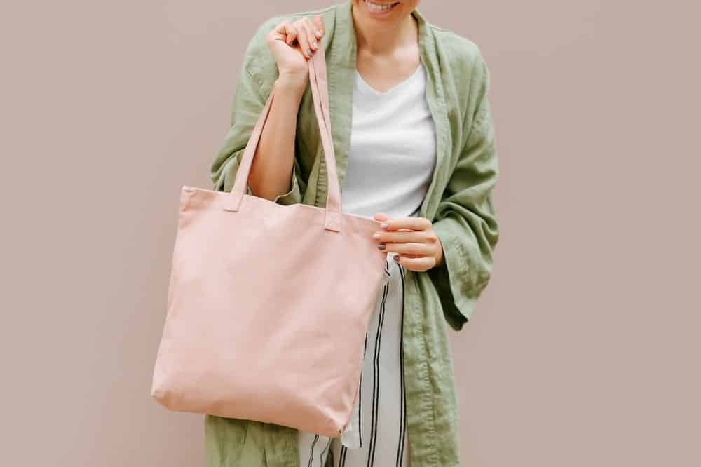 Woman holding canvas tote bag.