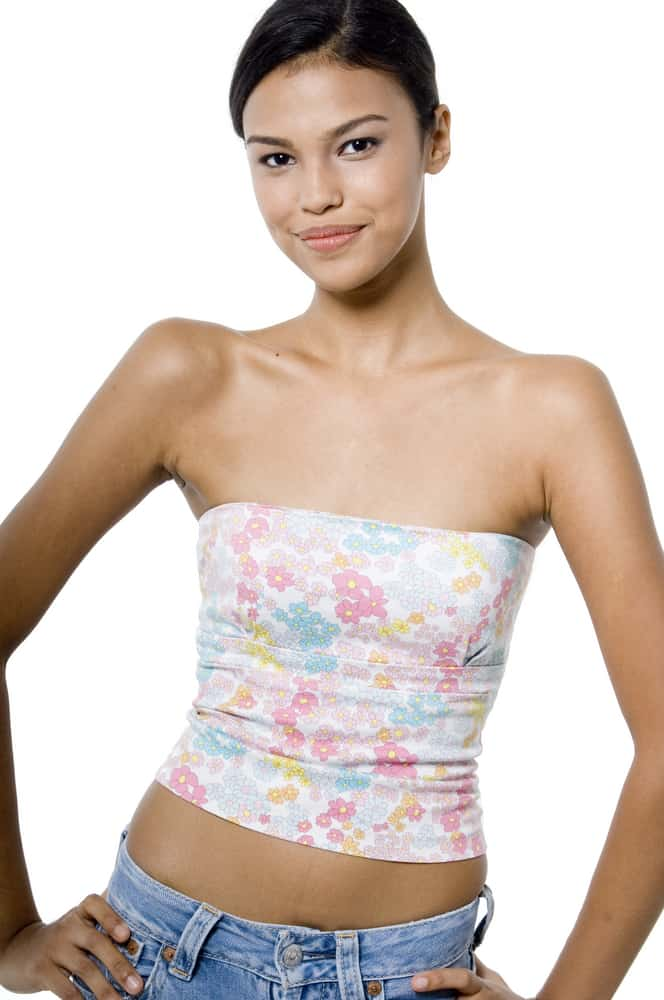 Woman wearing a flower print tube top poses against the white backdrop.