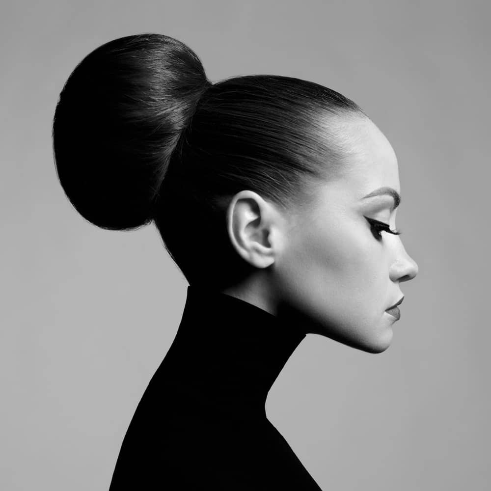 Woman in a bun hairstyle wearing a black turtleneck sweater.