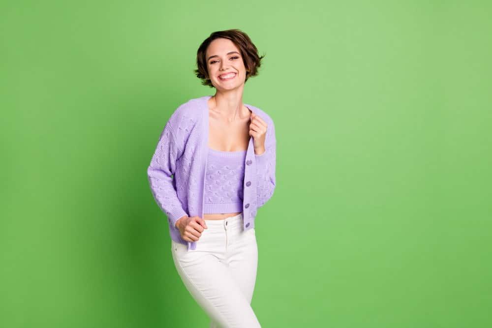 Woman in a purple twinset sweater flashing a sweet smile.