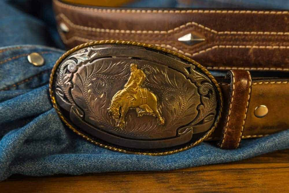 A belt with Vintage gold cowboy buckle on it.