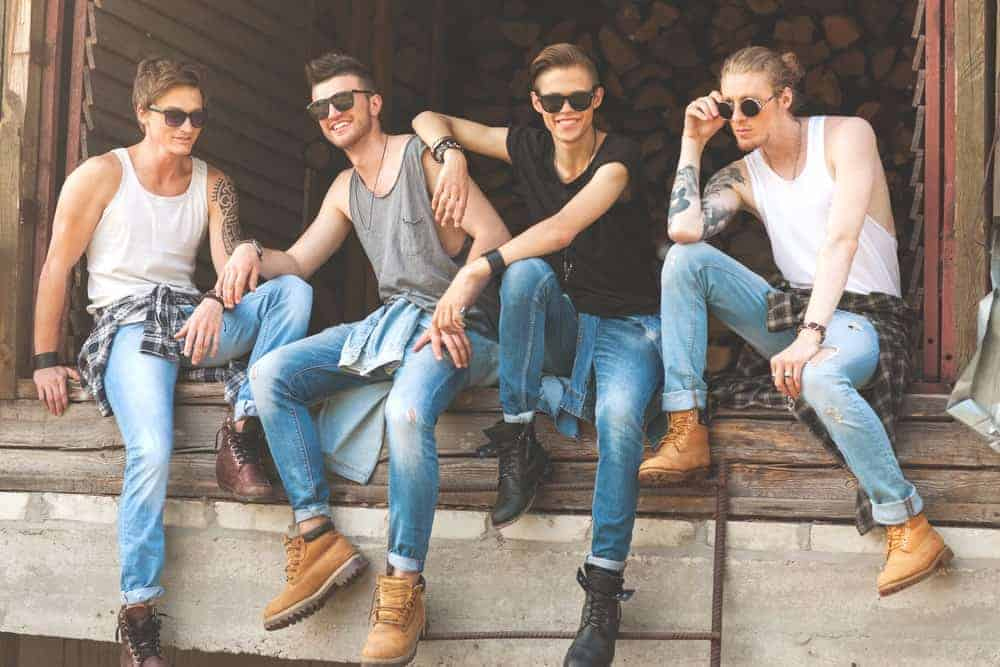 Four young men dressed in jeans of various styles, sitting on a ledge.