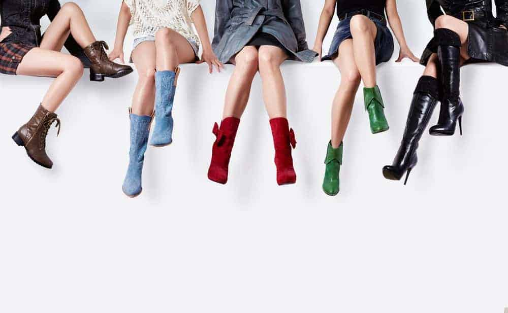 Women sitting on a white wall with multicolored boots.