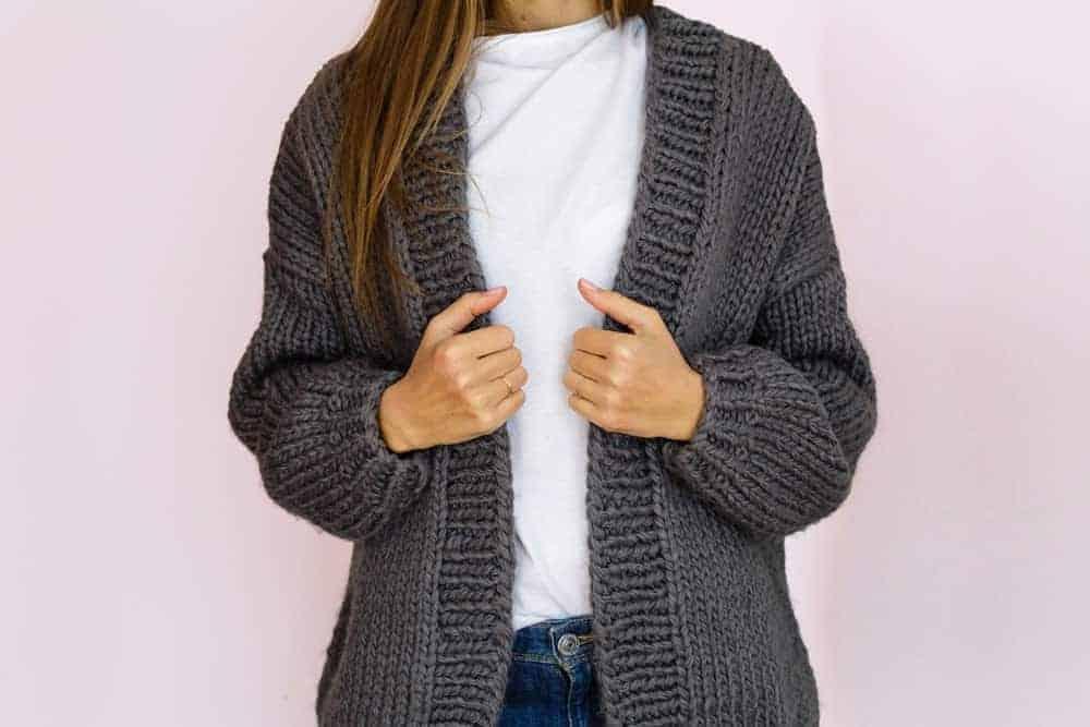 A woman wearing a gray knit cardigan.