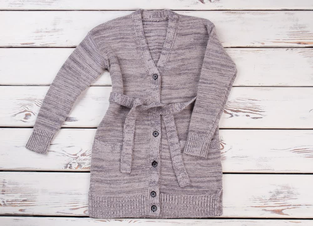 A gray belted cardigan on a wooden surface.