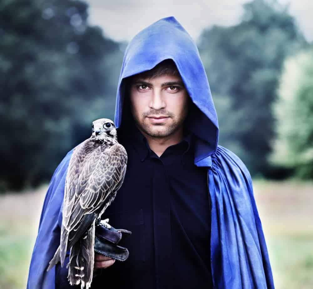 A falconer wearing a cloak.