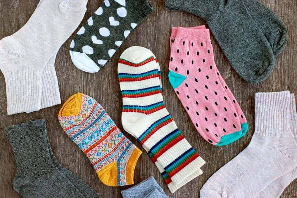 A variety of socks on a wooden surface.