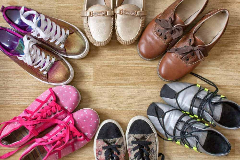 A variety of shoes arranged on a hardwood flooring.