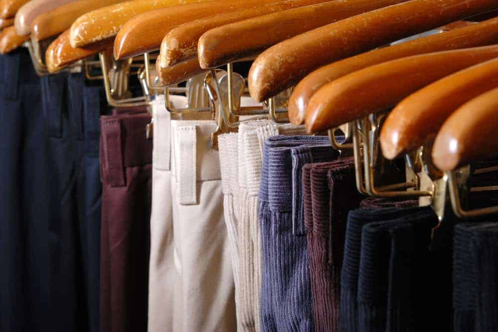Pants and trousers hanging in hangers on a rack.