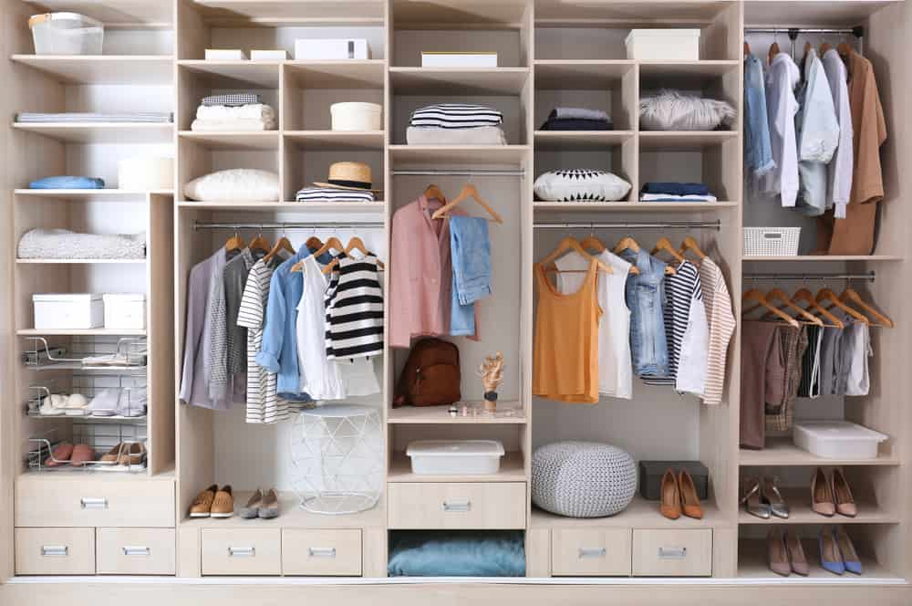 Built-in wardrobe filled with clothes and shoes.