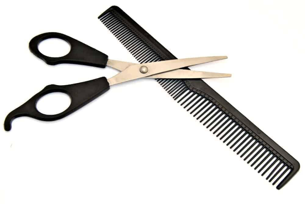 A black barber's comb with a pair of scissors.