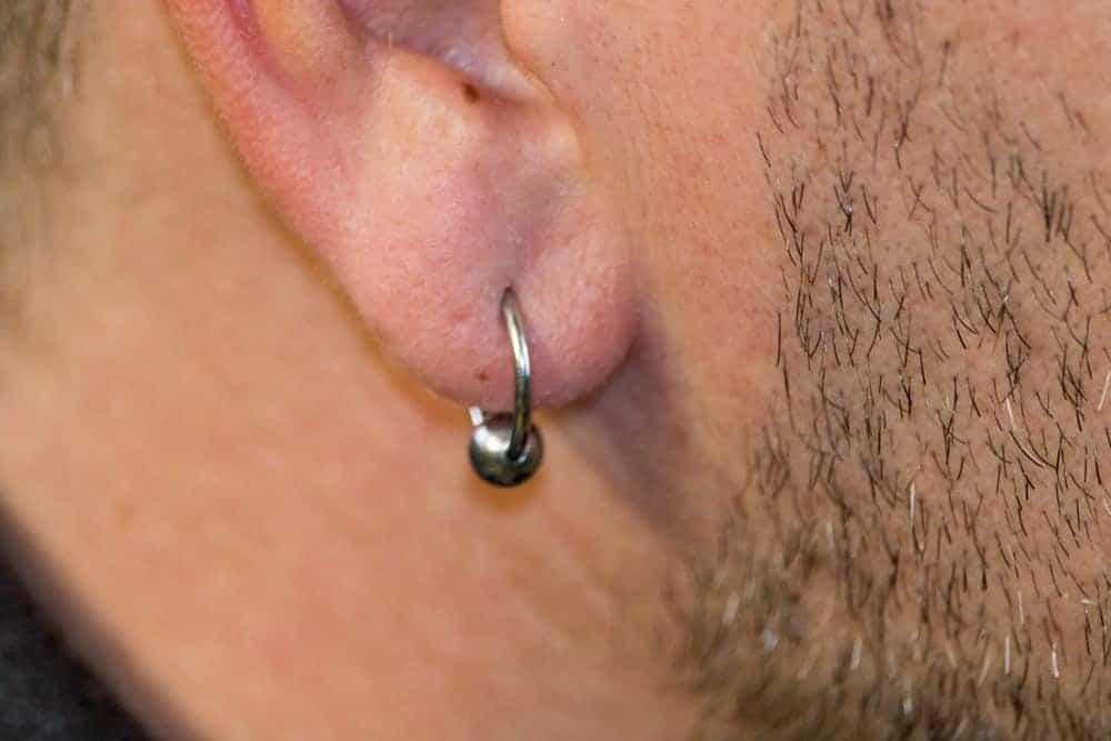 A close look at a man's ear with ear lobe piercing.