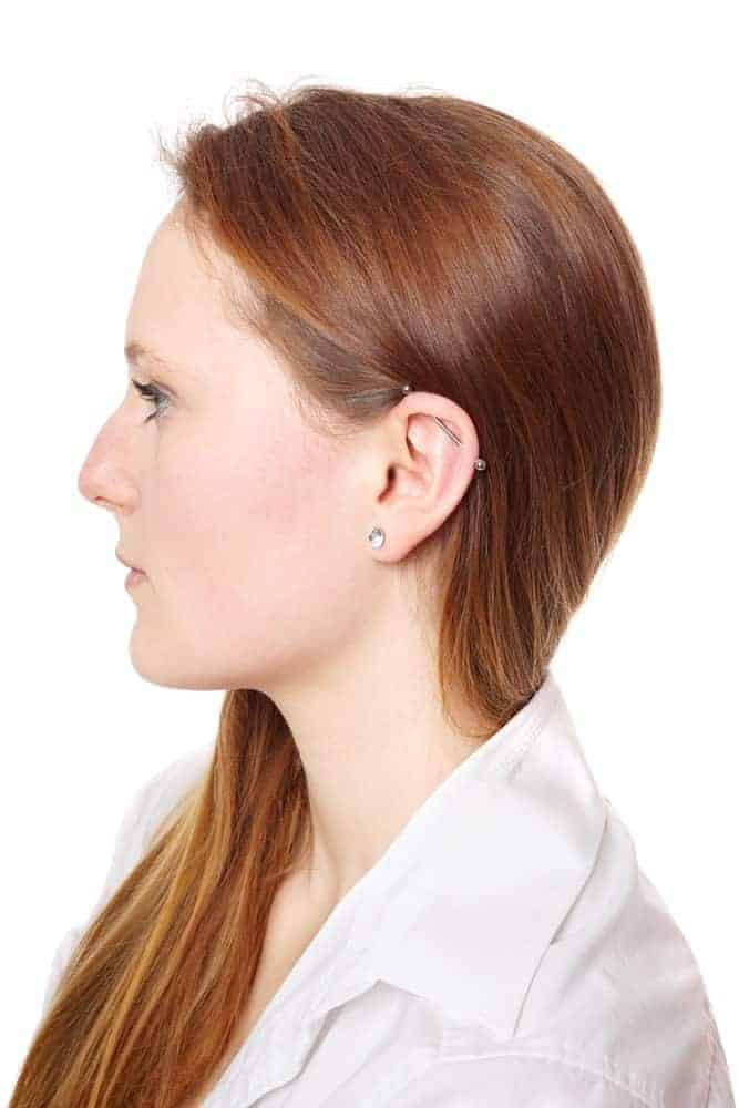 A look at the side of the woman wearing industrial earring.