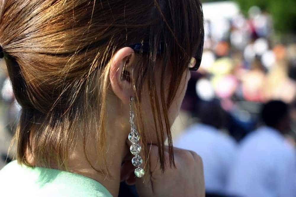 A woman wearing dangling earrings.