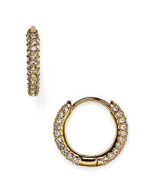 A pair of gold huggies earrings with diamond accents.