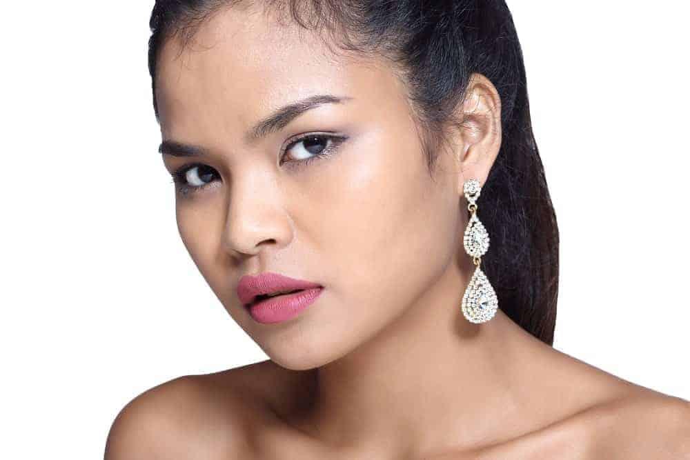 A woman wearing teardrop earrings.
