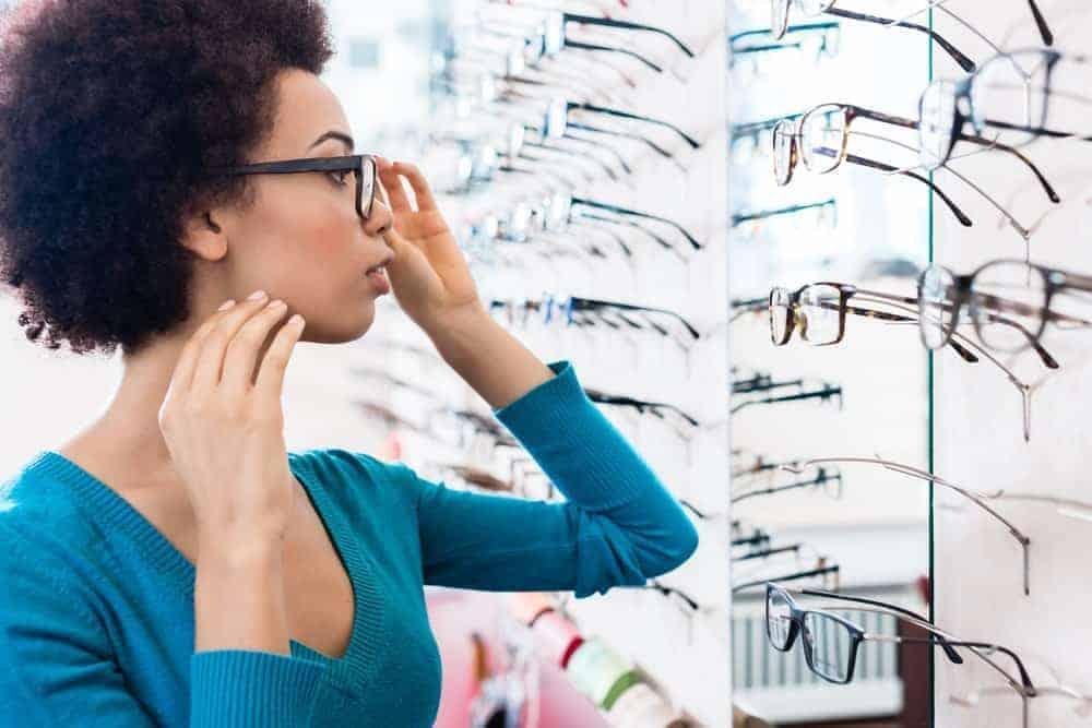 A woman browsing through various eyeglasses on display.