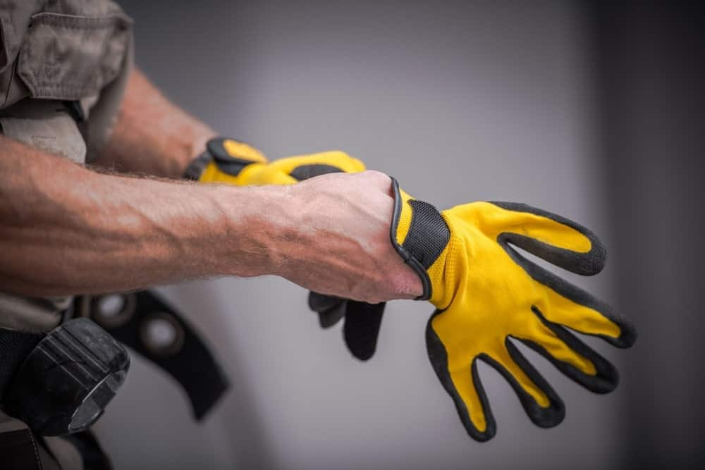A man putting a pair of yellow utility gloves.