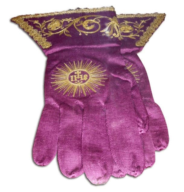 A pair of pink gloves with religious iconography embroidered on it.