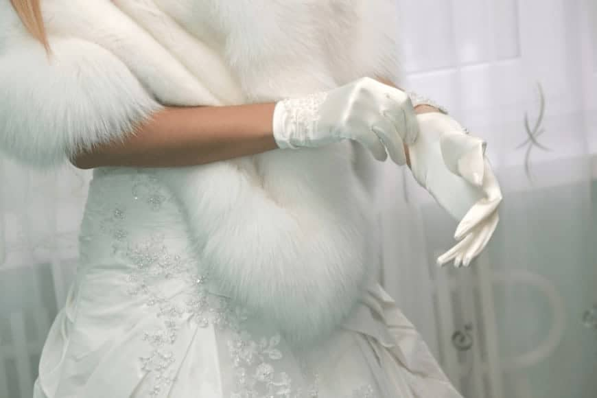 A woman putting on her white silk gloves.