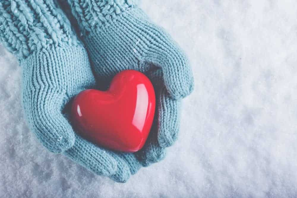 A pair of warm gloved hands holding a plastic heart.
