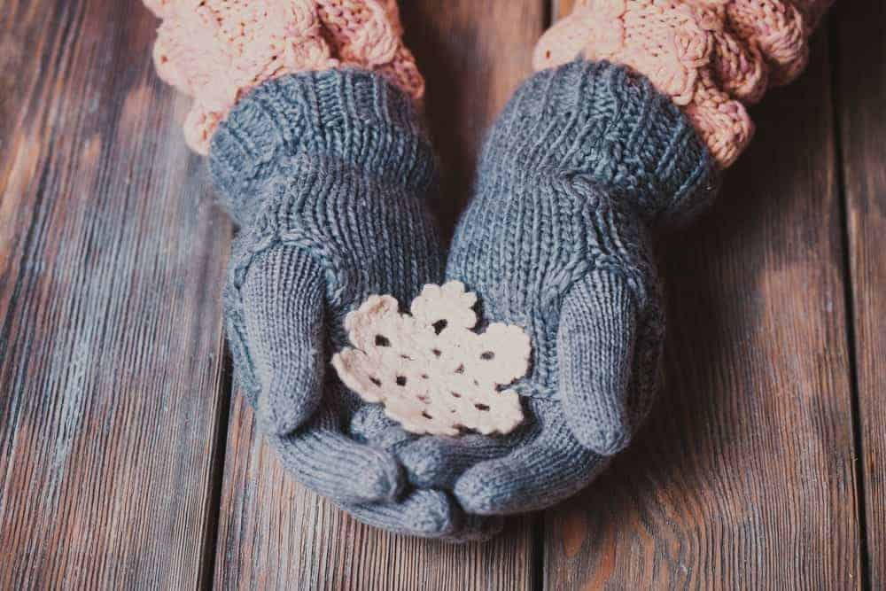 A warm and comfortable pair of knit Christmas gloves holding a knit snowflake.