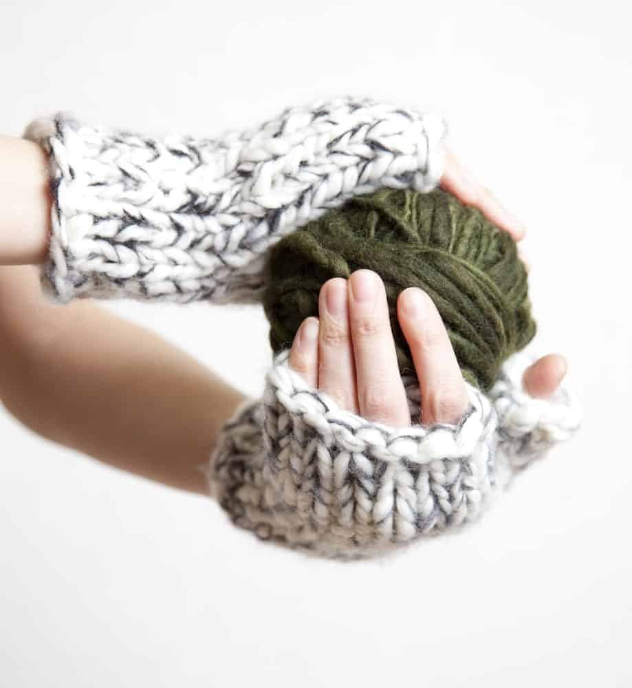 A pair of hands wearing wrist warmers and holding a ball of yarn.