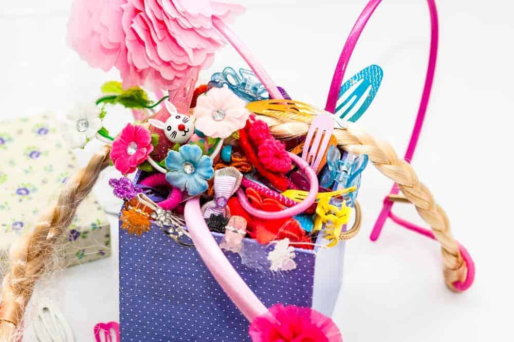 A variety of hair accessories in one container.