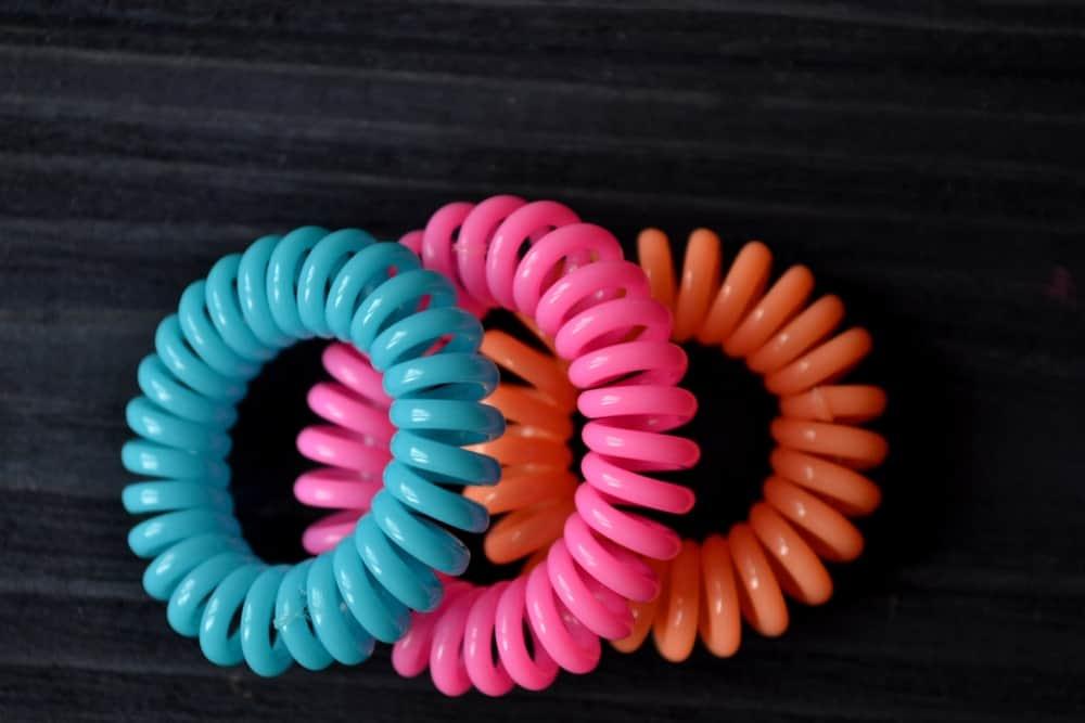 A set of plastic elastic ties against black background.