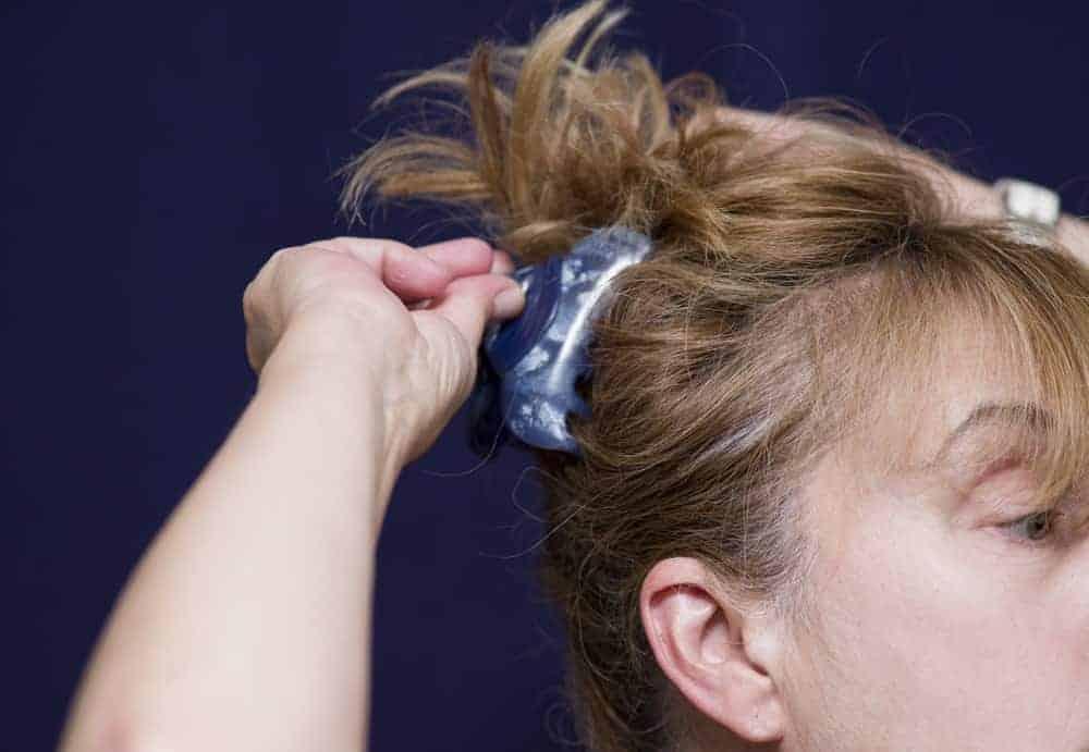 A woman putting on a hair clip.