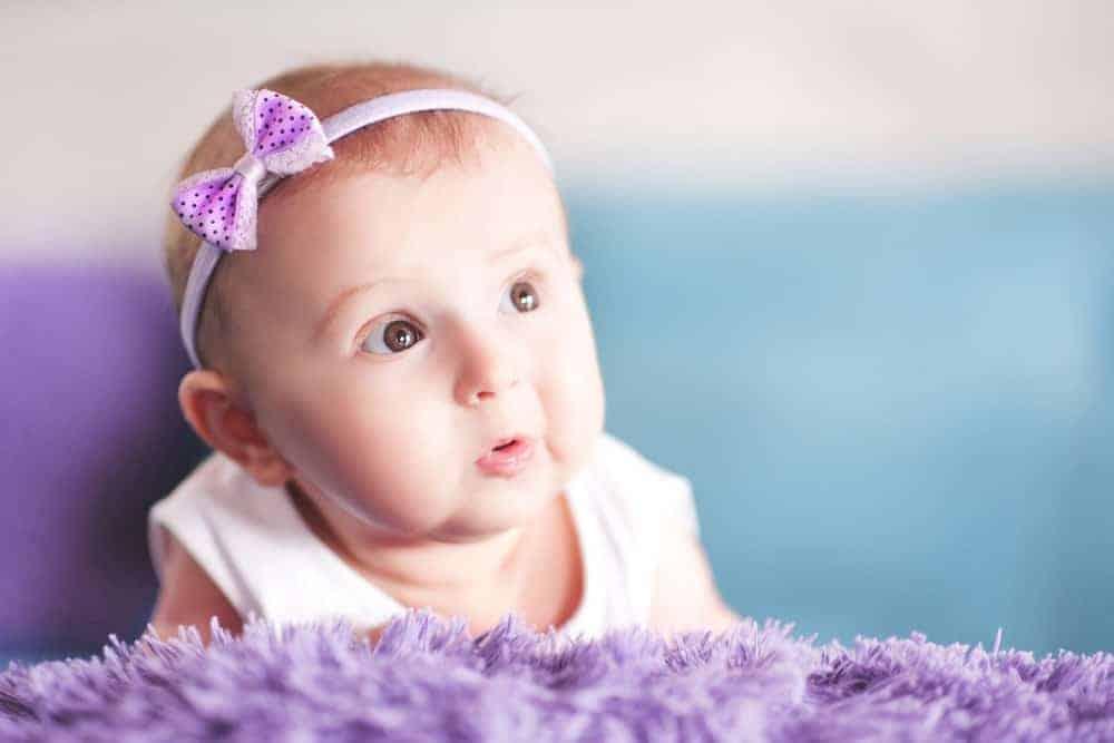 A cute baby wearing a purple ribbon headband.