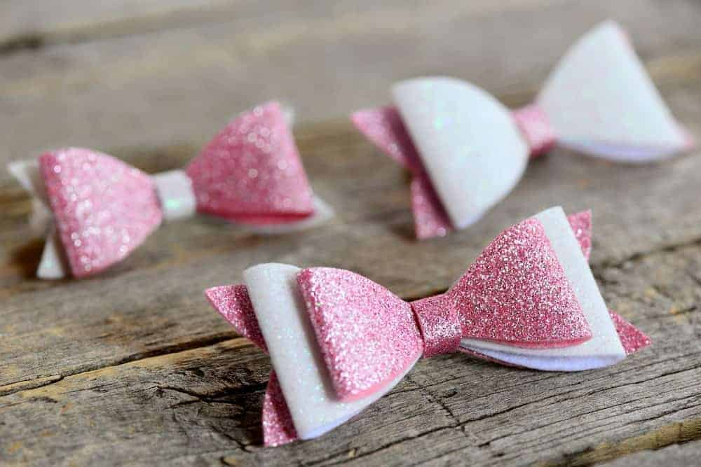 Three pink and white hair bows on a wooden surface.