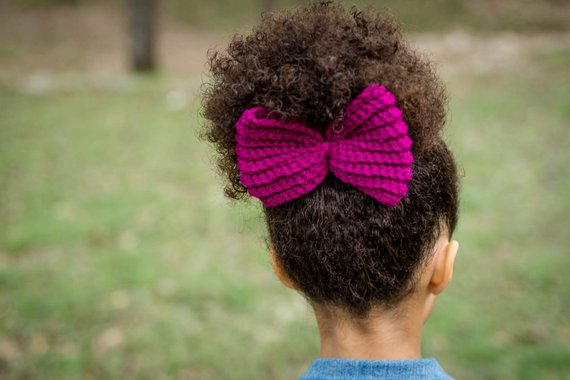 A woman wearing a hair bow made of yarn.