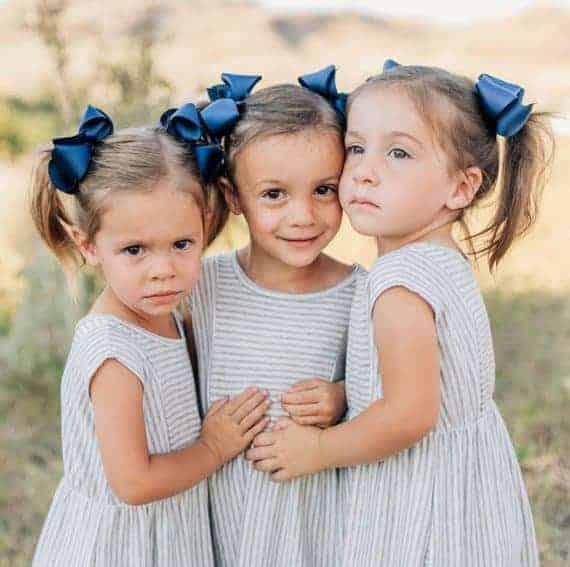 Three girls wearing grosgrain hair bows.
