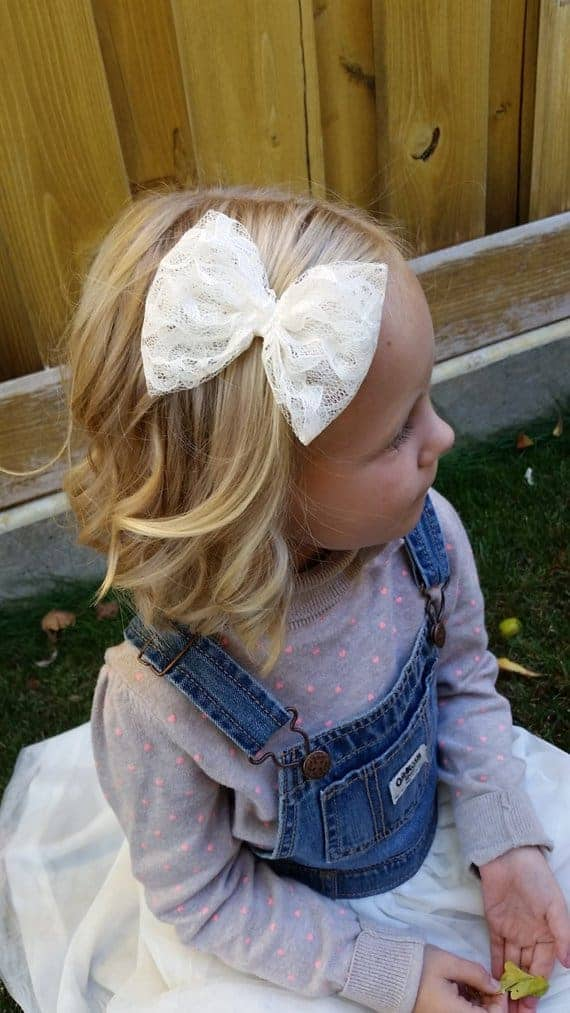 A girl wearing a lace hair bow.